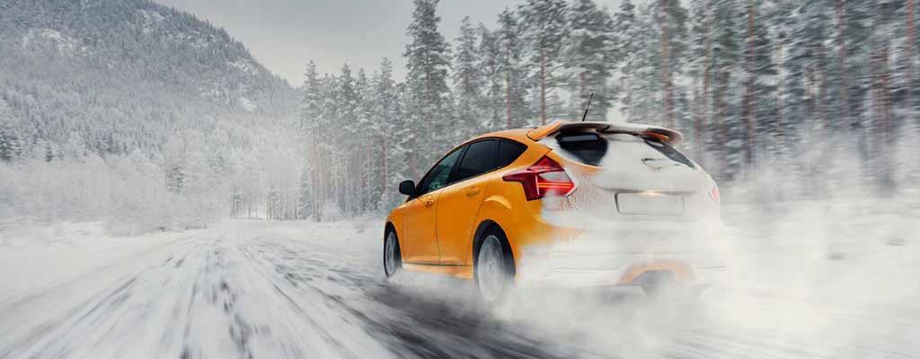 Fotografija prikazuje avto v zimskih razmerah, ko ima dolito tekočino za vetrobransko steklo, antifriz, snežne verige in poln akumulator.