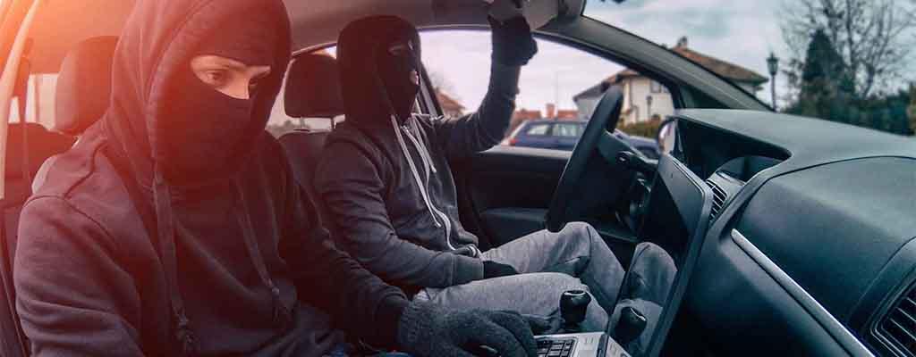 Fotografija prikazuje tatova na delu, ko kradeta avto.