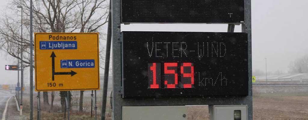 Fotografija prikazuje moč vetra na primorski cesti.