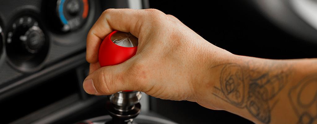 Na fotografiji je roka voznika, ki med vožnjo počiva na menjalniku.