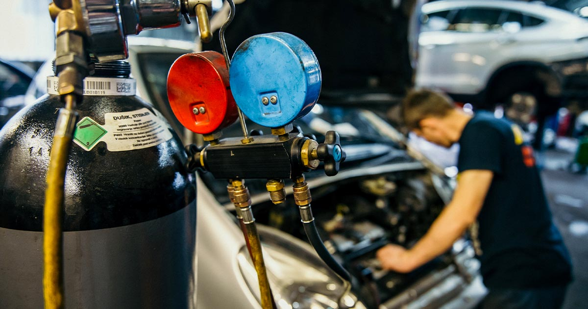 Na fotografiji je avtomehanik iz Avtocentra Avtostop, medtem ko opravlja polnjenje klime na avtomobilu.
