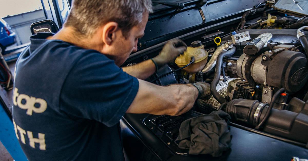 Na fotografiji je avtomehanik iz Avtocentra Avtostop, ujet medtem ko opravlja redni servis avta.