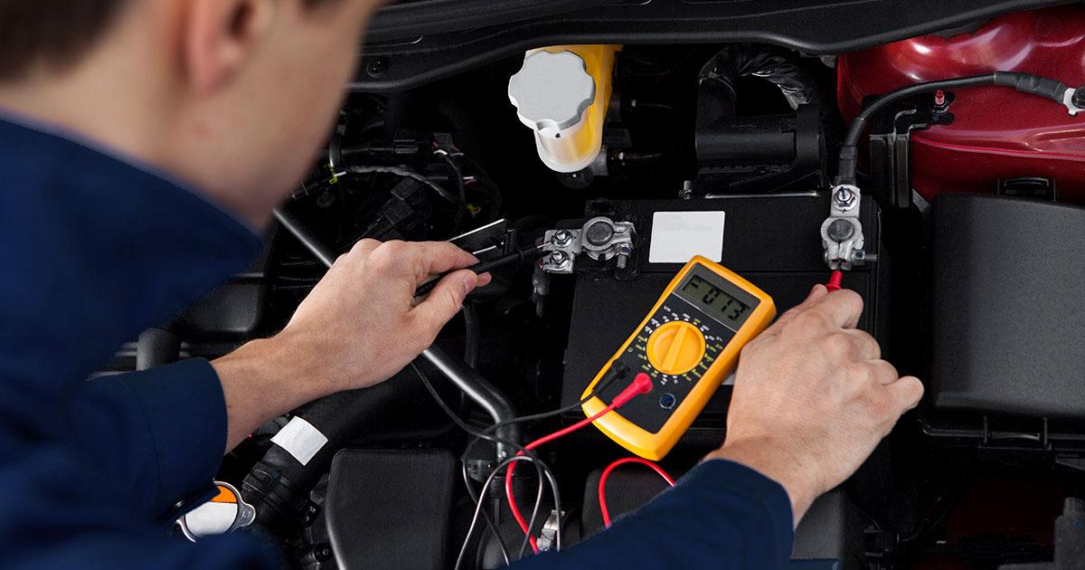 Fotografija prikazuje serviserja, ki s testerjem meri moč akumulatorja.