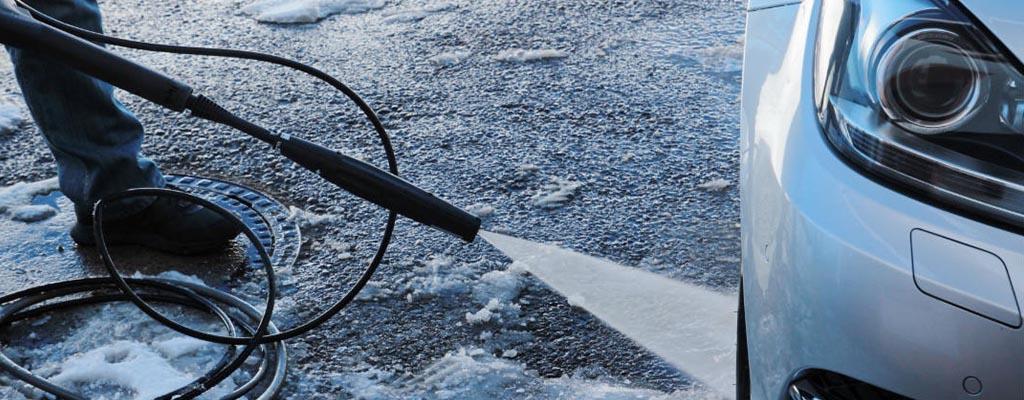 Fotografija prikazuje ročno čiščenje avtomobila pozimi.