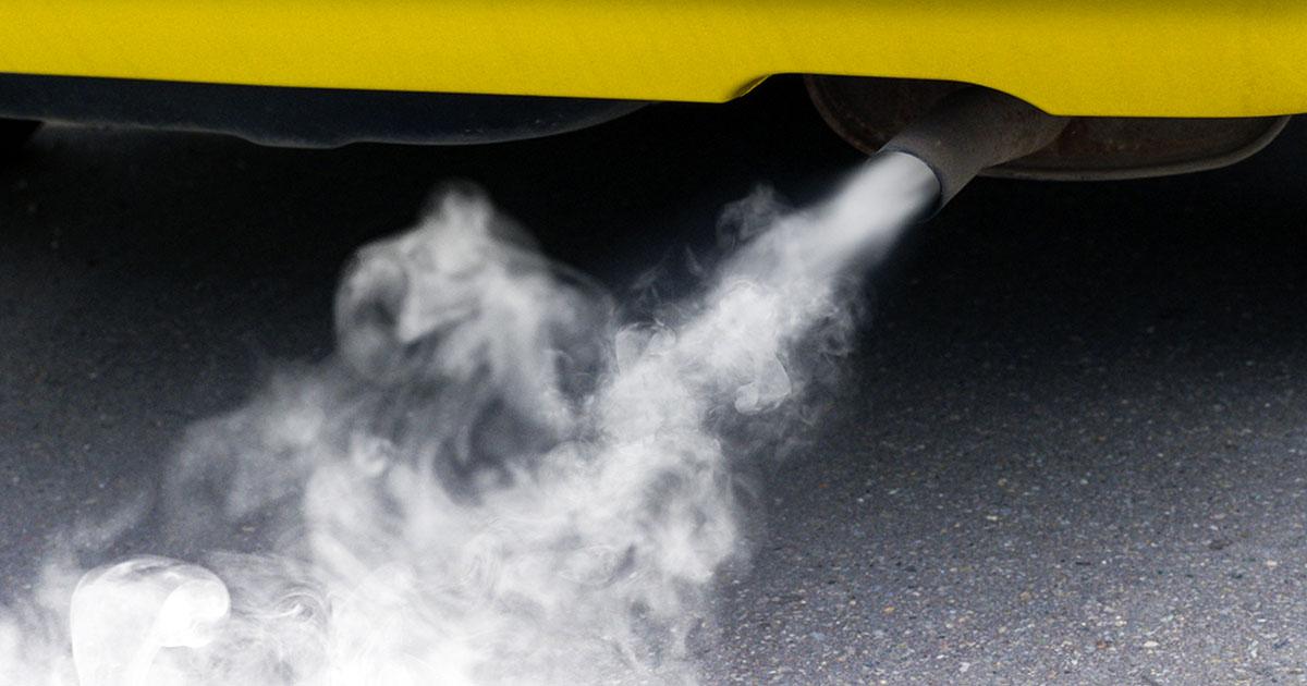 Na fotografiji je izpušni sistem avta, iz katerega se močno kadi.