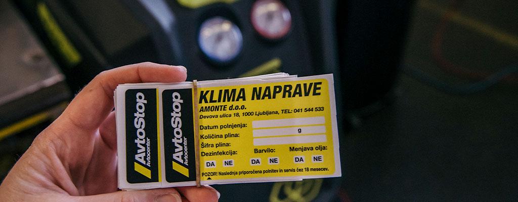 Na fotografiji je nalepka, ki dokazuje, da bila klima v avtu servisirana.